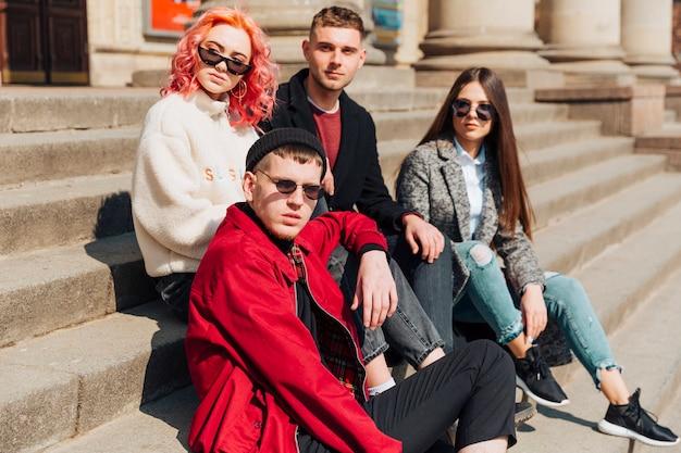 Jóvenes amigos sentados en las escaleras de piedra en la calle de la ciudad