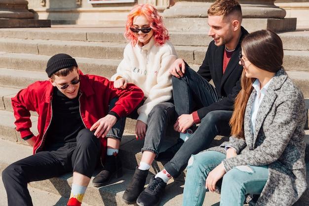 Jóvenes amigos sentados en las escaleras de piedra y divirtiéndose
