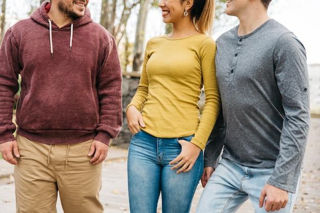 Jóvenes amigos sonriendo mientras caminan en ropa casual