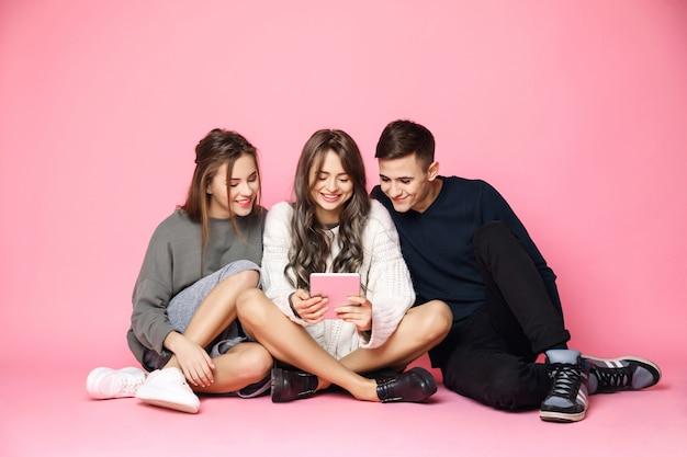 Jóvenes amigos sonriendo mirando tableta en rosa