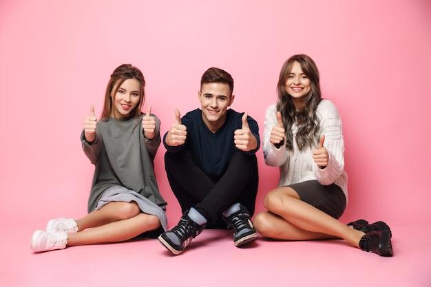 Jóvenes amigos sonriendo mostrando bien sentado en el piso rosa
