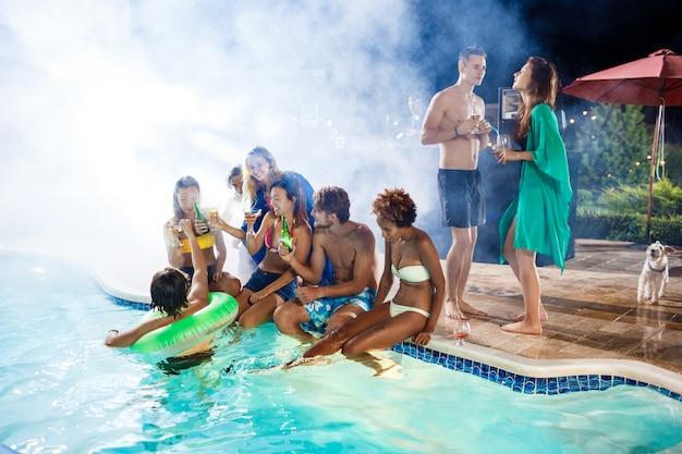 Jóvenes amigos sonriendo, regocijándose, descansando en la fiesta junto a la piscina