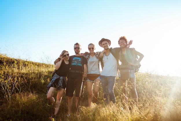 Jóvenes amigos sonriendo, regocijándose, de pie en el campo