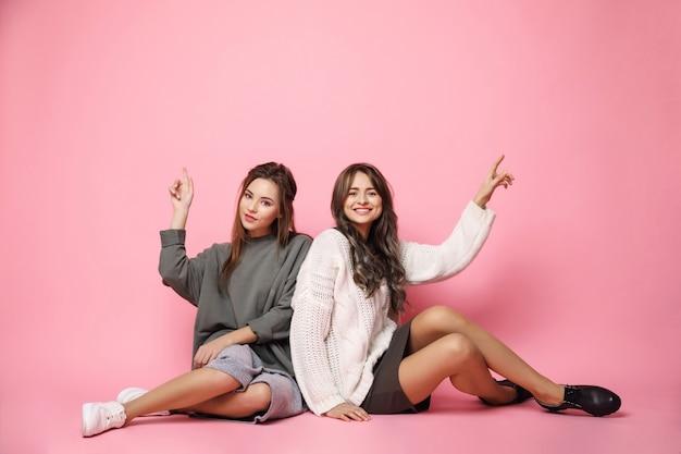 Jóvenes amigos sonriendo señalando con el dedo hacia arriba en rosa