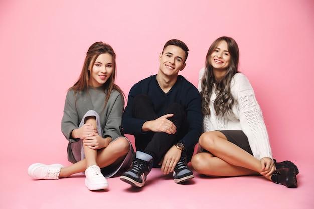 Jóvenes amigos sonriendo sentado en el piso rosa