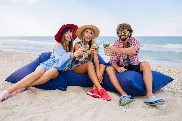 Jóvenes amigos sonrientes de vacaciones sentados en bolsas de frijoles en una fiesta en la playa