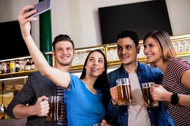 Jóvenes amigos tomando selfie mientras sostiene la jarra de cerveza