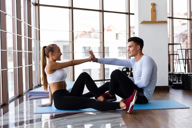 Jóvenes amigos trabajando juntos en la clase de fitness