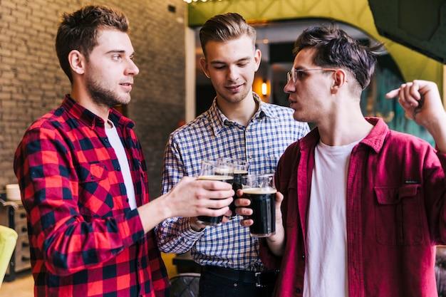 Jóvenes amigos varones disfrutando de la bebida en el restaurante