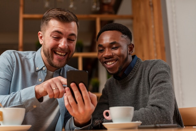 Jóvenes amigos varones mirando en el móvil