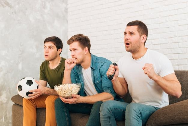 Jóvenes amigos viendo partido de fútbol en televisión con expresiones serias.