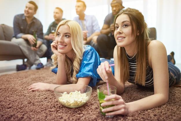 Jóvenes amigos viendo la televisión juntos relajándose