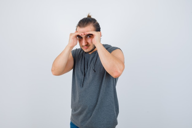 Los jóvenes aptos para hombres tomados de la mano en la cabeza para ver claramente en una sudadera con capucha sin mangas y mirando enfocado, vista frontal.