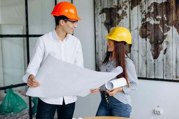 Jóvenes arquitectos colegas están analizando planos mientras trabajan en un nuevo proyecto