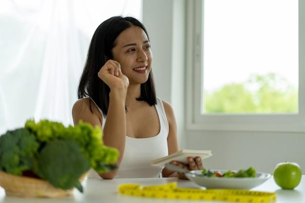 Las jóvenes asiáticas están perdiendo peso y eligen comer frutas y verduras para gozar de buena salud. las mujeres están planeando una dieta saludable para comer en cada comida. concepto de dieta
