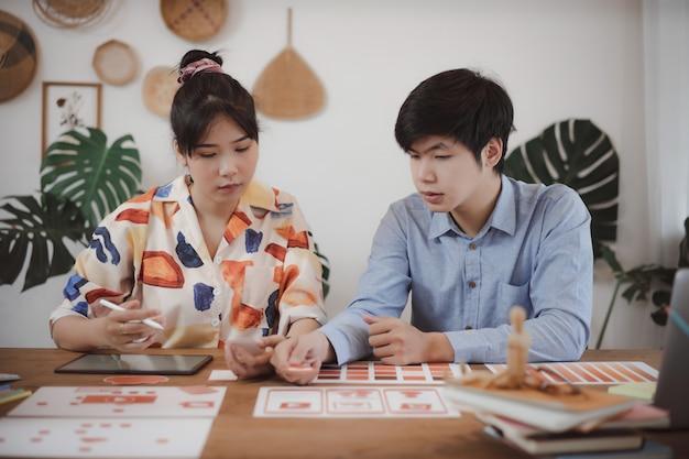 Jóvenes asiáticos creativos desarrolladores de aplicaciones móviles teamworks debate sobre la pantalla de diseño de plantillas móviles para la planificación creativa del desarrollo de aplicaciones móviles.