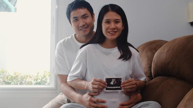Jóvenes asiáticos embarazadas pareja muestran y mirando la foto de ultrasonido bebé en el vientre. mamá y papá se sienten felices sonriendo pacíficos mientras cuidan al niño acostado en el sofá en la sala de estar en casa.