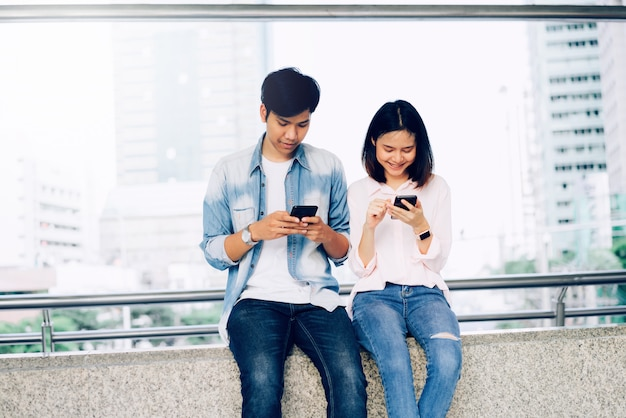 Los jóvenes asiáticos están usando un teléfono inteligente y sonriendo mientras están sentados en el tiempo libre. concepto de tecnología