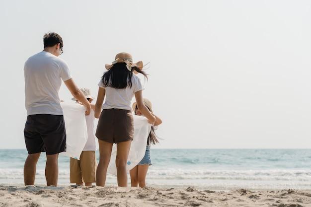 Jóvenes asiáticos felices activistas familiares recogiendo residuos plásticos y caminando en la playa. los voluntarios de asia ayudan a mantener la naturaleza limpia de basura. concepto sobre problemas de contaminación de conservación ambiental.