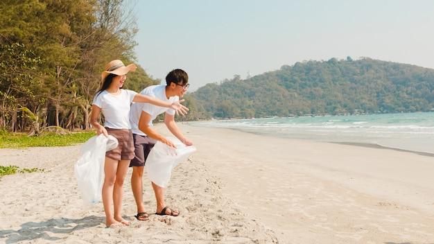 Jóvenes asiáticos felices activistas familiares recogiendo residuos plásticos en la playa. los voluntarios de asia ayudan a mantener la naturaleza limpia y recoger la basura. concepto sobre problemas de contaminación de conservación ambiental.