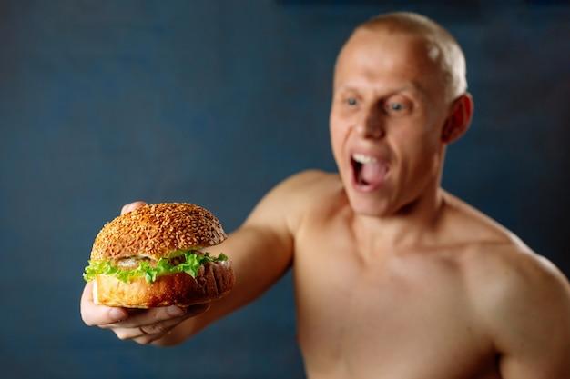 Los jóvenes atletas musculosos fuertes hombres miran la hamburguesa con queso y comida chatarra poco saludable. come proteína de hamburguesa