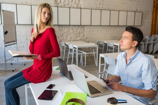 Jóvenes atractivos que trabajan juntos en línea en la sala de oficina de trabajo conjunto de espacios abiertos