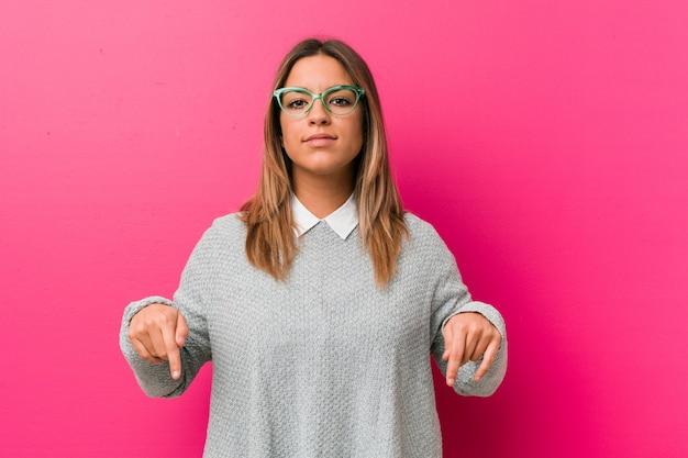 Jóvenes auténticos carismáticos personas reales mujer contra una pared apunta hacia abajo con los dedos, sentimiento positivo.