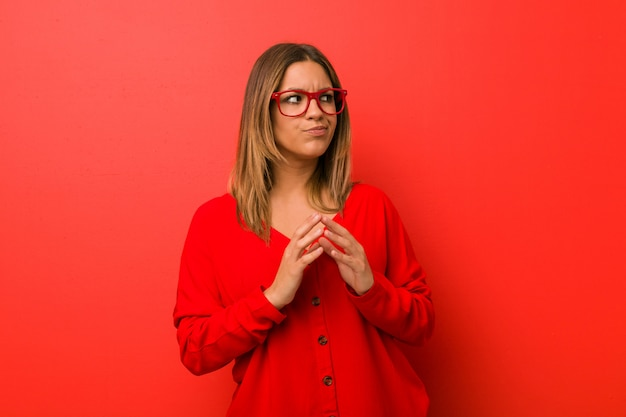Jóvenes auténticos carismáticos personas reales mujer contra una pared haciendo un plan en mente, creando una idea.