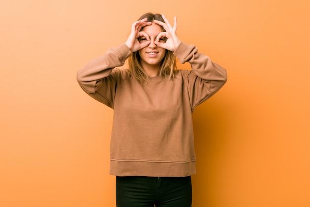 Jóvenes auténticos carismáticos personas reales mujer contra una pared que muestra bien firmar sobre los ojos