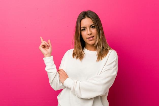 Jóvenes auténticos carismáticos personas reales mujer contra una pared sonriendo alegremente señalando con el dedo lejos.