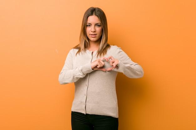 Jóvenes auténticos carismáticos personas reales mujer contra una pared sonriendo y mostrando una forma de corazón con las manos.