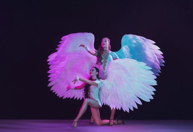 Jóvenes bailarinas con alas de ángel blancas en colores neón. modelos agraciados, mujeres bailando, posando.