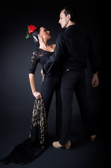 Jóvenes bailarines de flamenco en hermoso vestido sobre fondo negro.