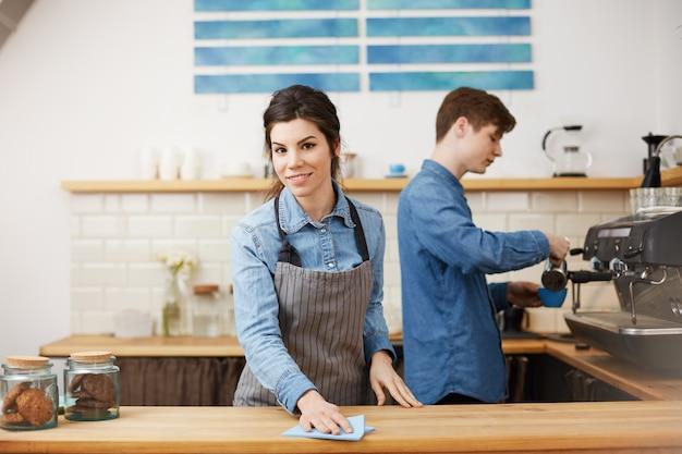 Jóvenes baristas agradables en uniforme trabajando en barra de bar.