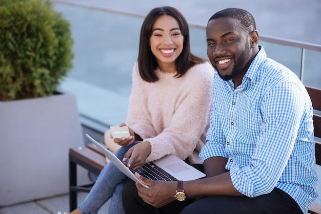 Jóvenes brillantes y maravillosos que encuentran el artículo perfecto que buscan en internet y usan tarjeta de crédito para el pago.