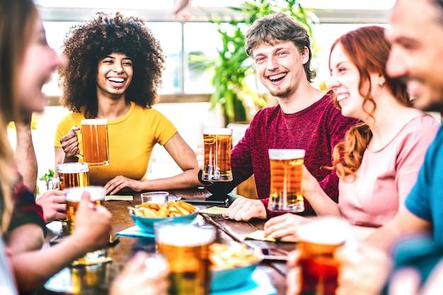 Los jóvenes brindando cerveza en la azotea del bar cervecería