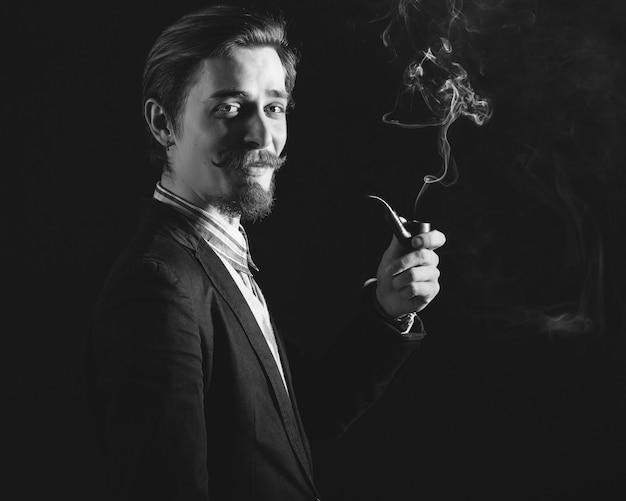 Jóvenes caballeros fuma una pipa