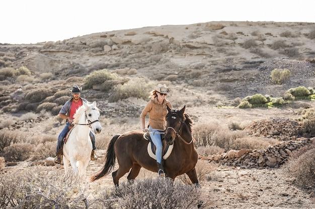 Los jóvenes a caballo haciendo excursión al atardecer - el foco principal en el rostro de la mujer