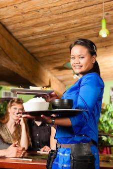 Jóvenes con camarera comiendo en restaurante tailandés