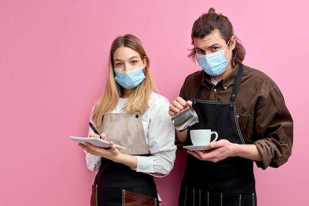 Los jóvenes camareros listos para servir a los clientes en la cafetería o restaurante, posan en la cámara aislada sobre fondo rosa