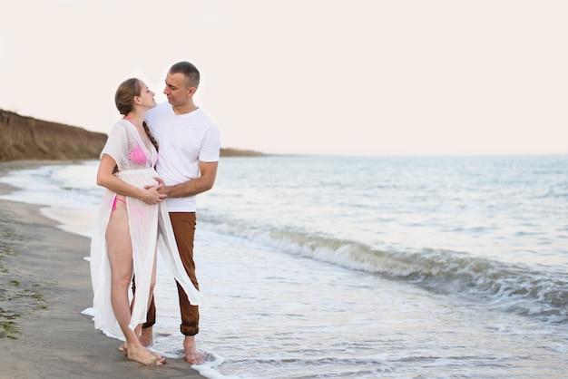 Jóvenes casados en la costa del mar. el esposo abraza a su esposa embarazada. tiempo antes del atardecer