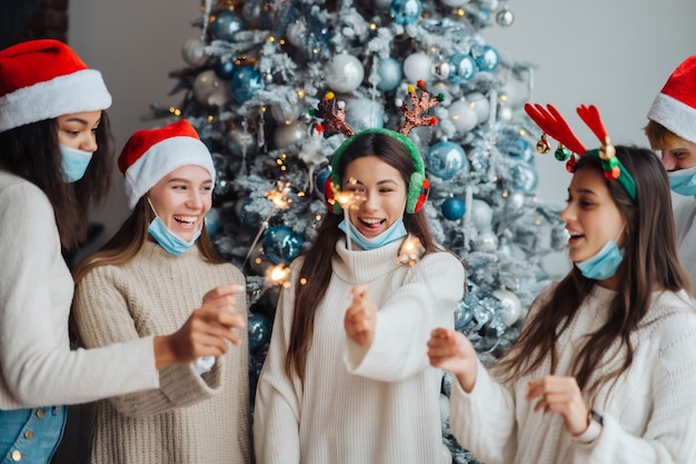 Jóvenes celebrando la víspera de año nuevo con bengalas, amigos multirraciales que se divierten en la celebración de la fiesta