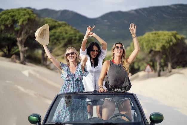 Jóvenes chicas españolas divirtiéndose mientras está de pie en un coche descapotable en una playa de arena