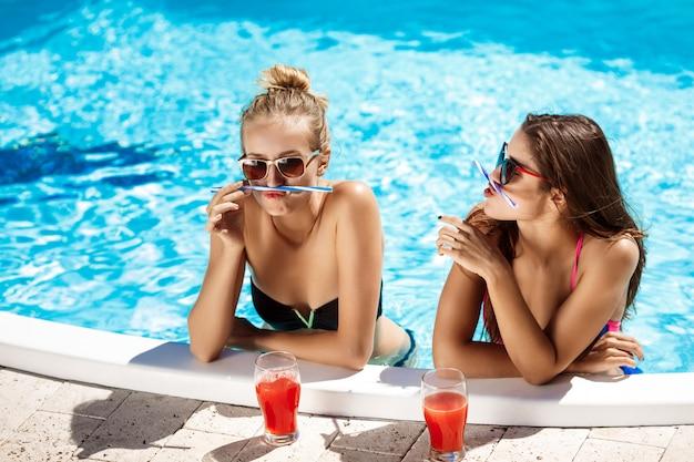 Jóvenes chicas guapas sonriendo, engañando, hablando, relajándose en la piscina.
