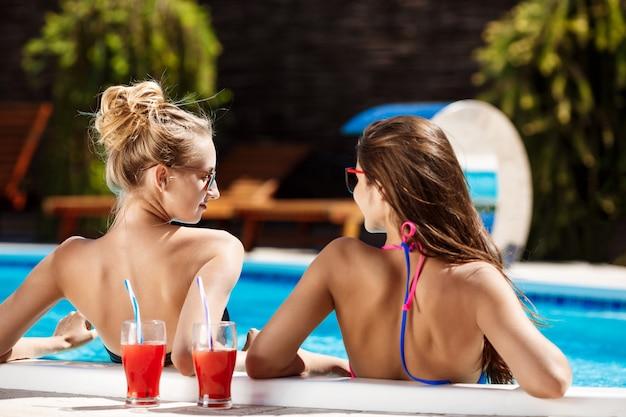 Jóvenes chicas guapas sonriendo, hablando, relajándose en la piscina.