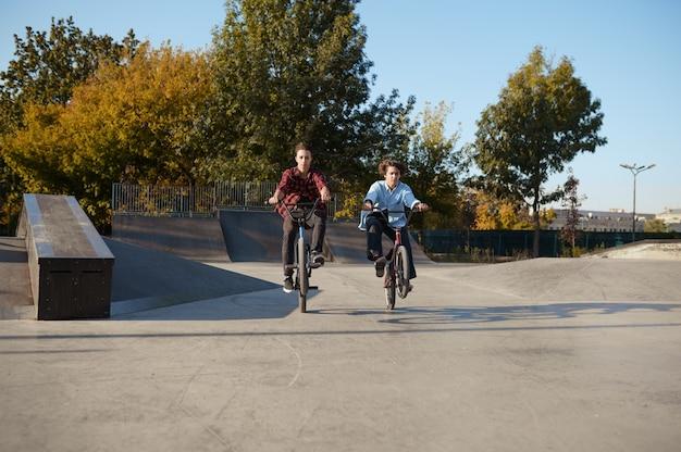 Jóvenes ciclistas de bmx haciendo trucos en el skatepark. deporte extremo en bicicleta, ejercicio de ciclo peligroso, paseos en la calle, ciclismo en el parque de verano