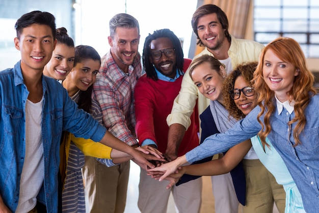 Jóvenes colegas acumulando sus manos