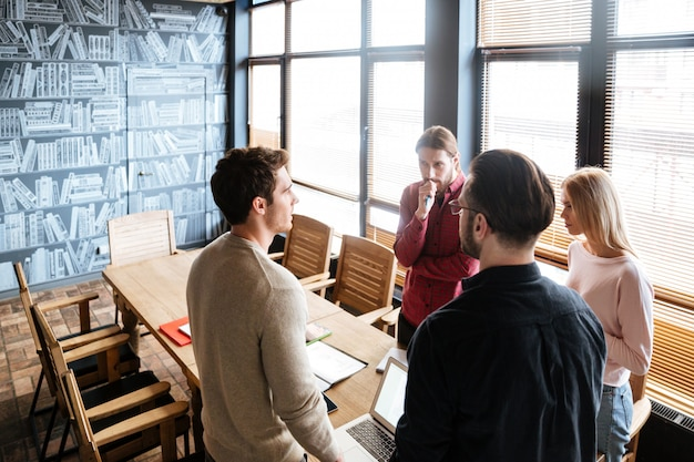 Jóvenes colegas atractivos de pie mientras trabaja