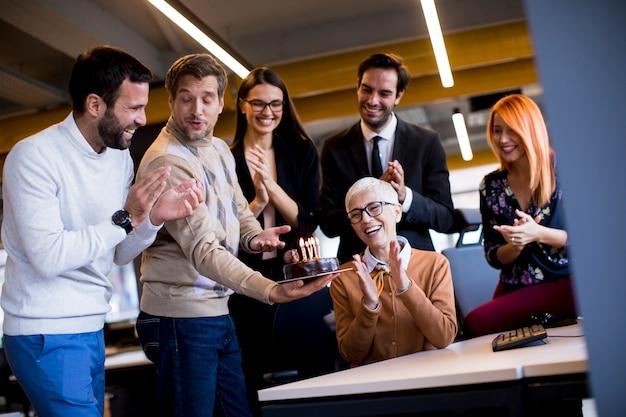 Jóvenes colegas celebran el cumpleaños de un colega mayor en la oficina y traen un pastel