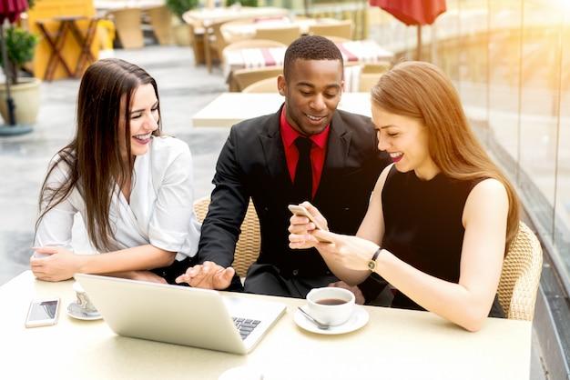 Jóvenes colegas diversos almorzando en el restaurante al aire libre